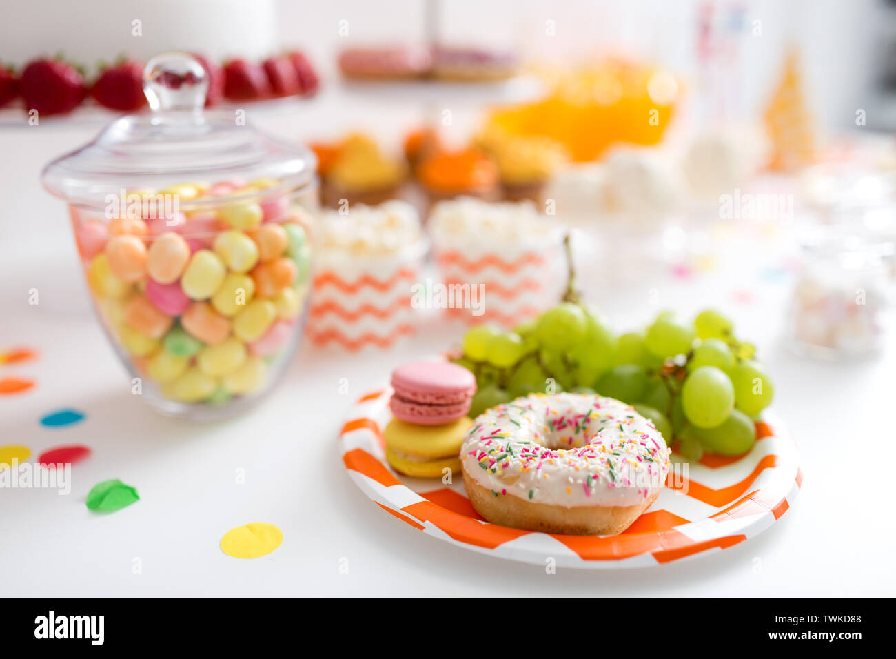 grapes, macarons and donut on party table - Stock Image