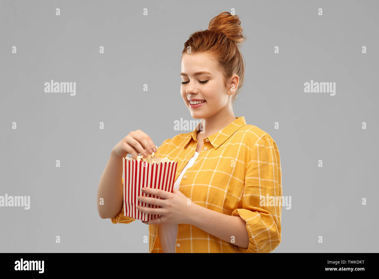 smiling red haired teenage girl eating popcorn - Stock Image