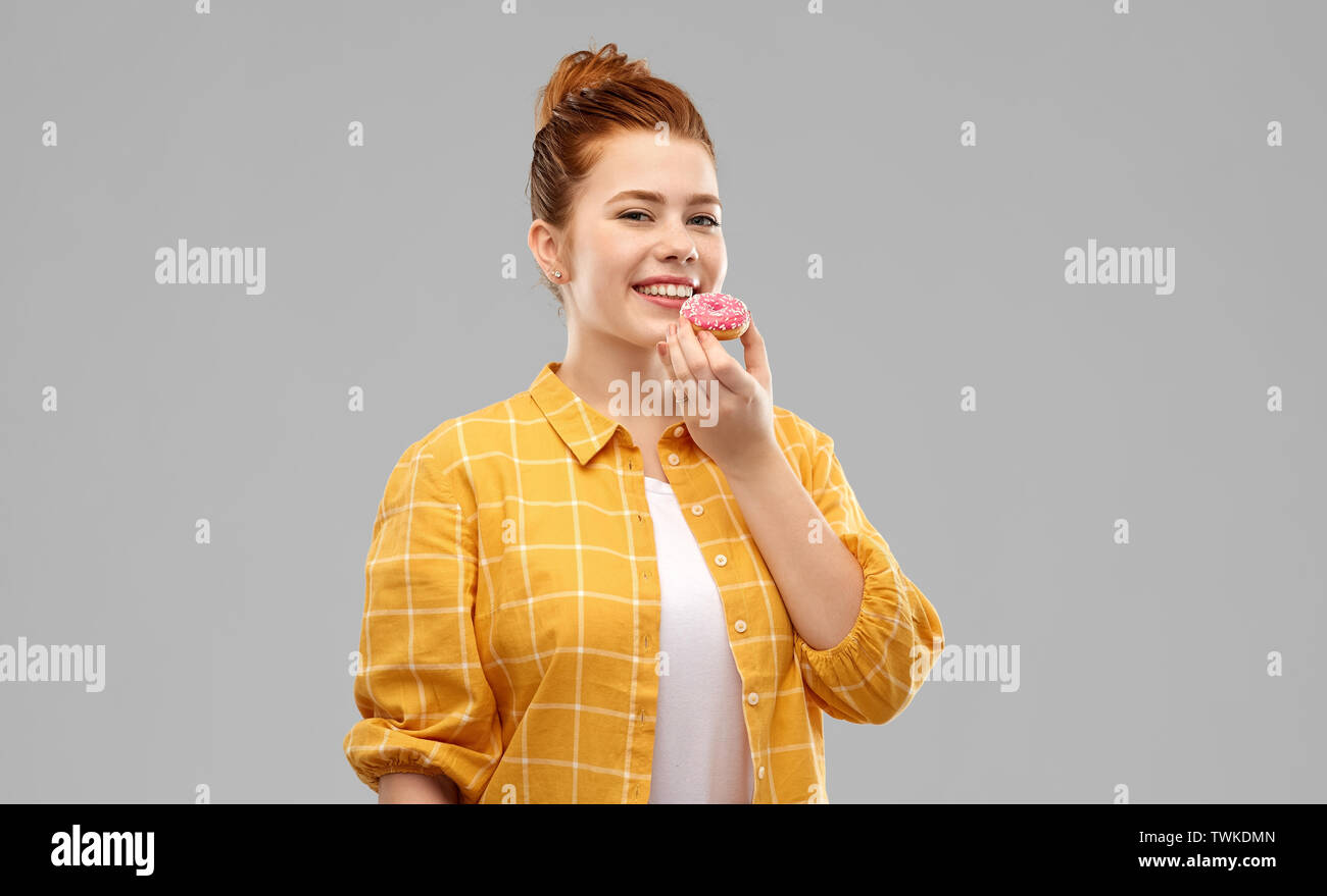 smiling red haired teenage girl eating donut - Stock Image