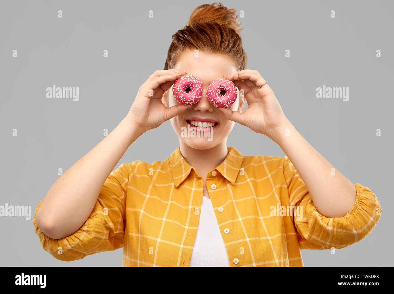 funny teenage girl with donuts instead of eyes - Stock Image