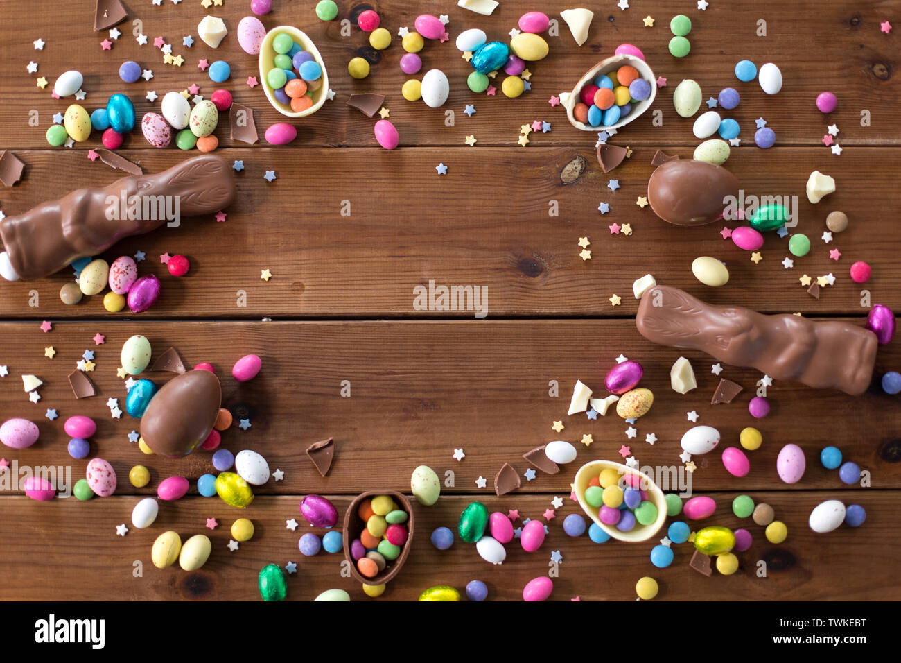 chocolate eggs, easter bunnies and candies on wood - Stock Image