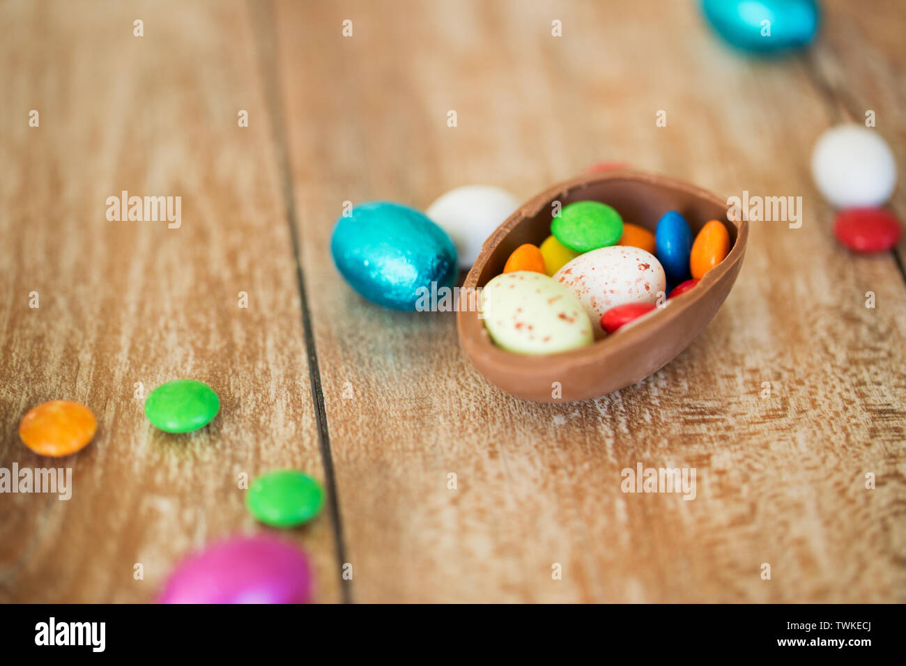 chocolate easter egg and candy drops on table - Stock Image