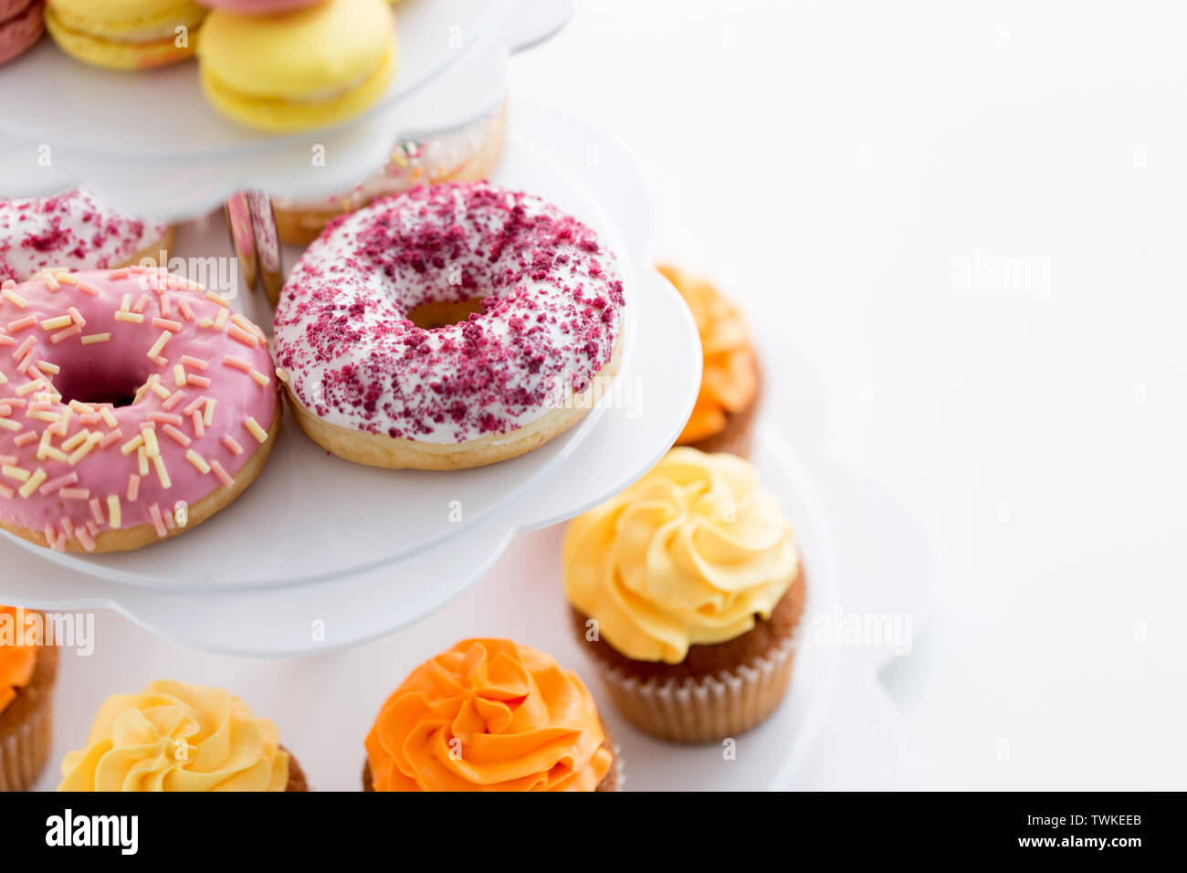 close up of glazed donuts and cupcakes on stand - Stock Image