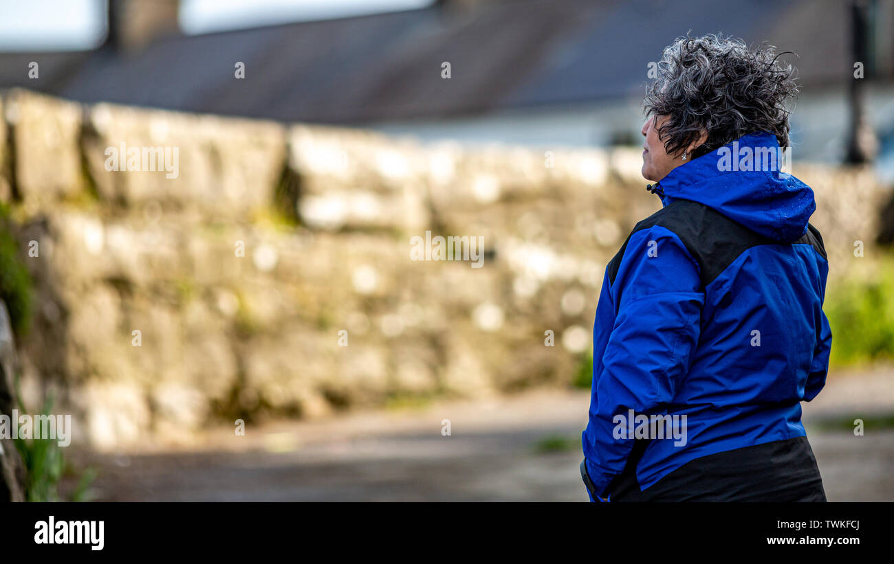 Beautiful and happy mature mexican woman with her hair tousled by the wind in a blue jacket, looking intently at a wall, with a blurred background, wo - Stock Image
