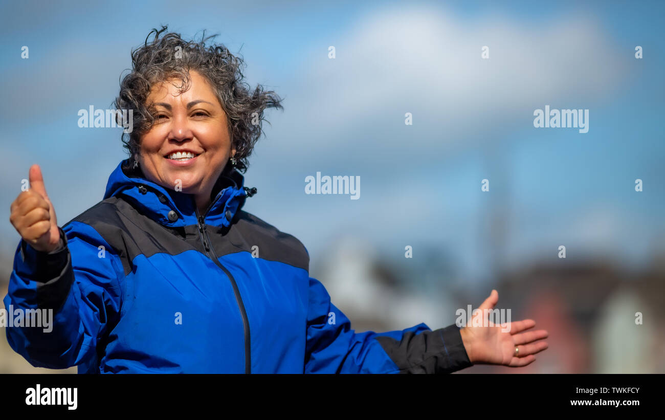 Beautiful happy mature mexican woman with her hair tousled by the wind with a blue jacket, making a sign of a very good day, wonderful sunny  day to e - Stock Image