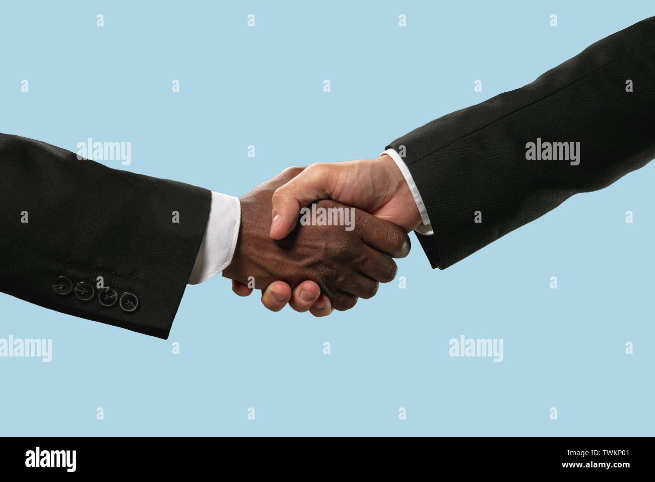 Sign of joint plans for the future. Teamwork and communications. Two male hands shaking isolated on blue studio background. Concept of help, partnership, friendship, relation, business, togetherness. Stock Photo