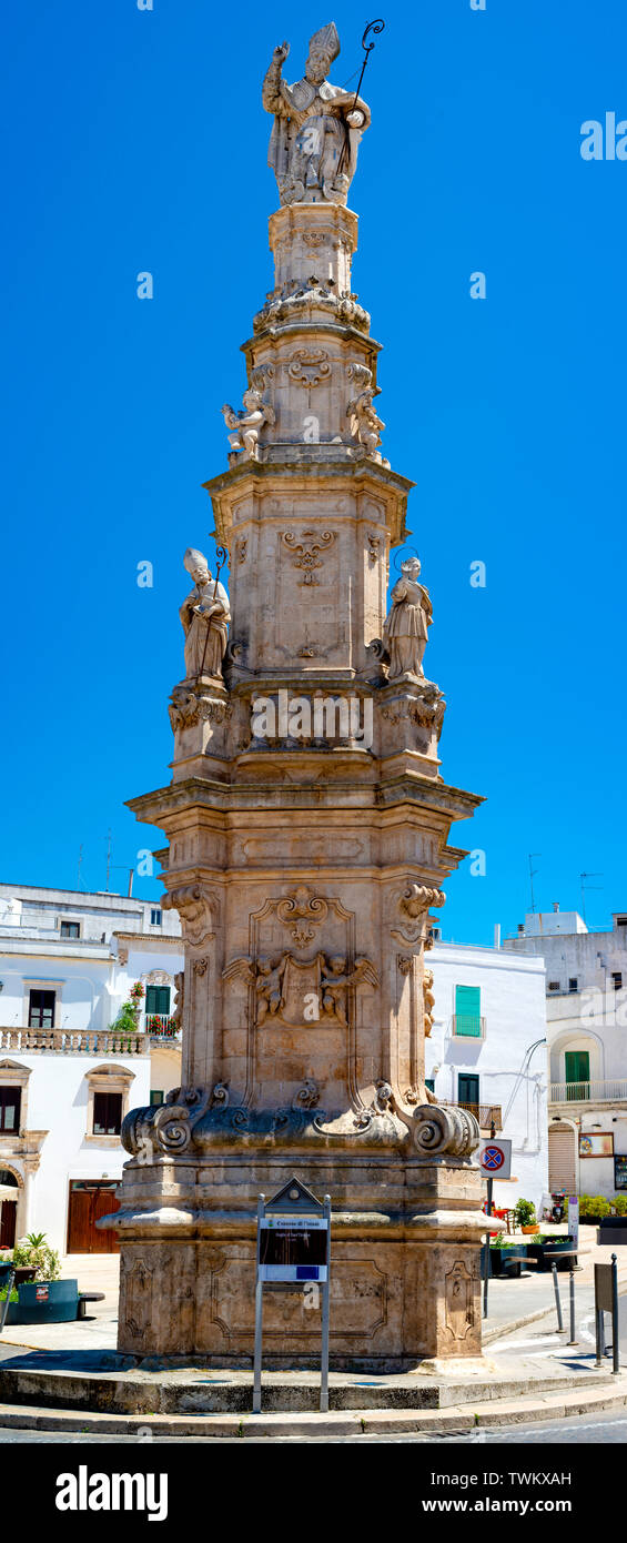A wide angle shot of the Tower of St. Horace (Guglia di Sant Oronzo) in Piazza della Liberta square - Stock Image