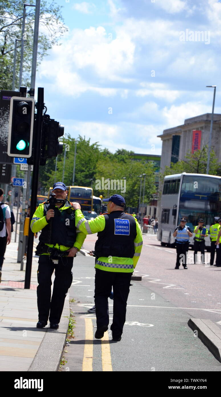 Police evidence gatherers film young people lobbying for action to prevent climate change at the  Manchester Youth Strike 4 Climate protest on June 21, 2019, in Manchester, uk. The group marched from St Peter's Square in the city centre to the University of Manchester. One of their demands is for the University to divest itself of investments in fossil fuels. - Stock Image