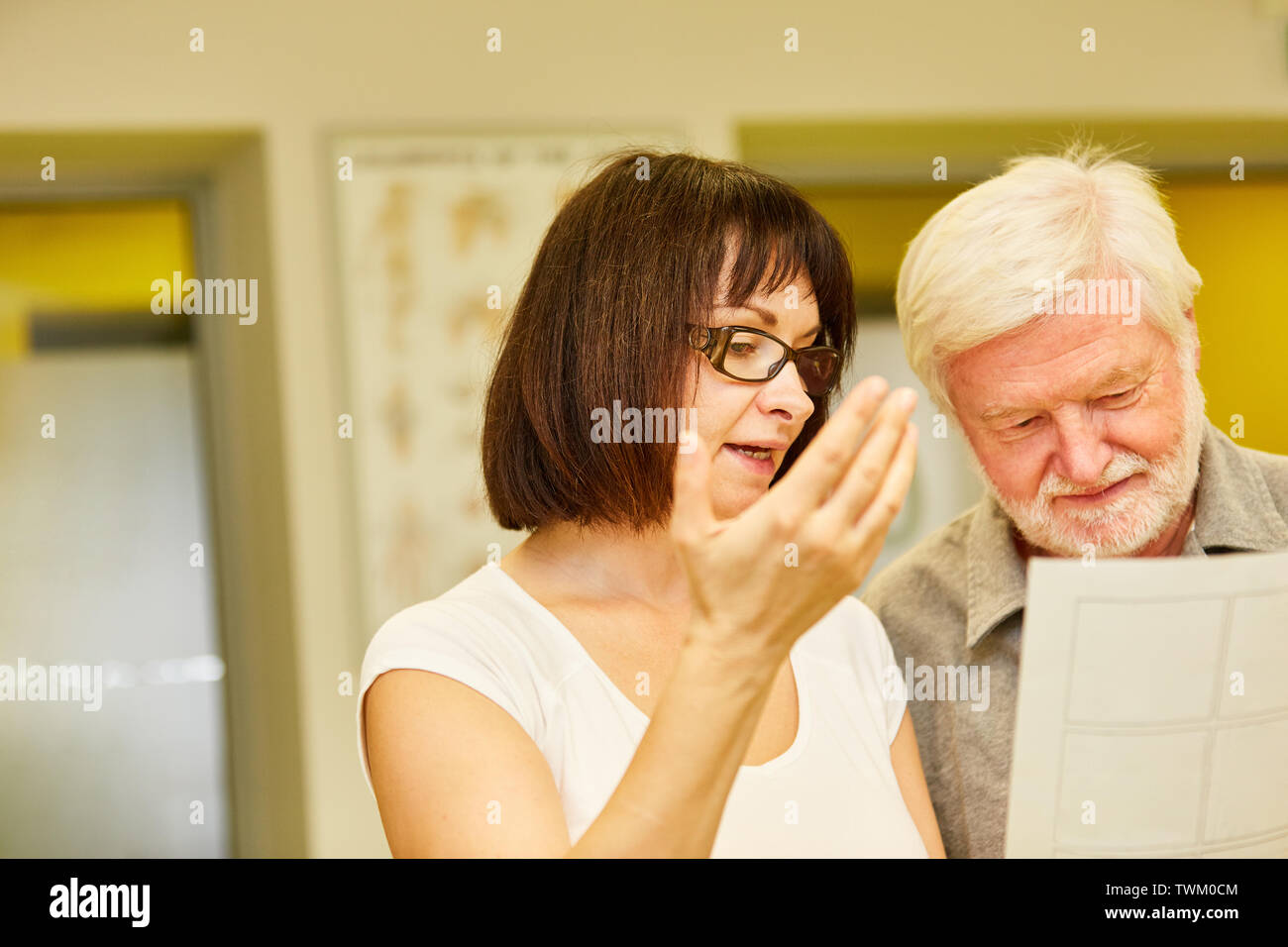 Doctor or physiotherapist shows senior man the treatment plan for the physiotherapy - Stock Image