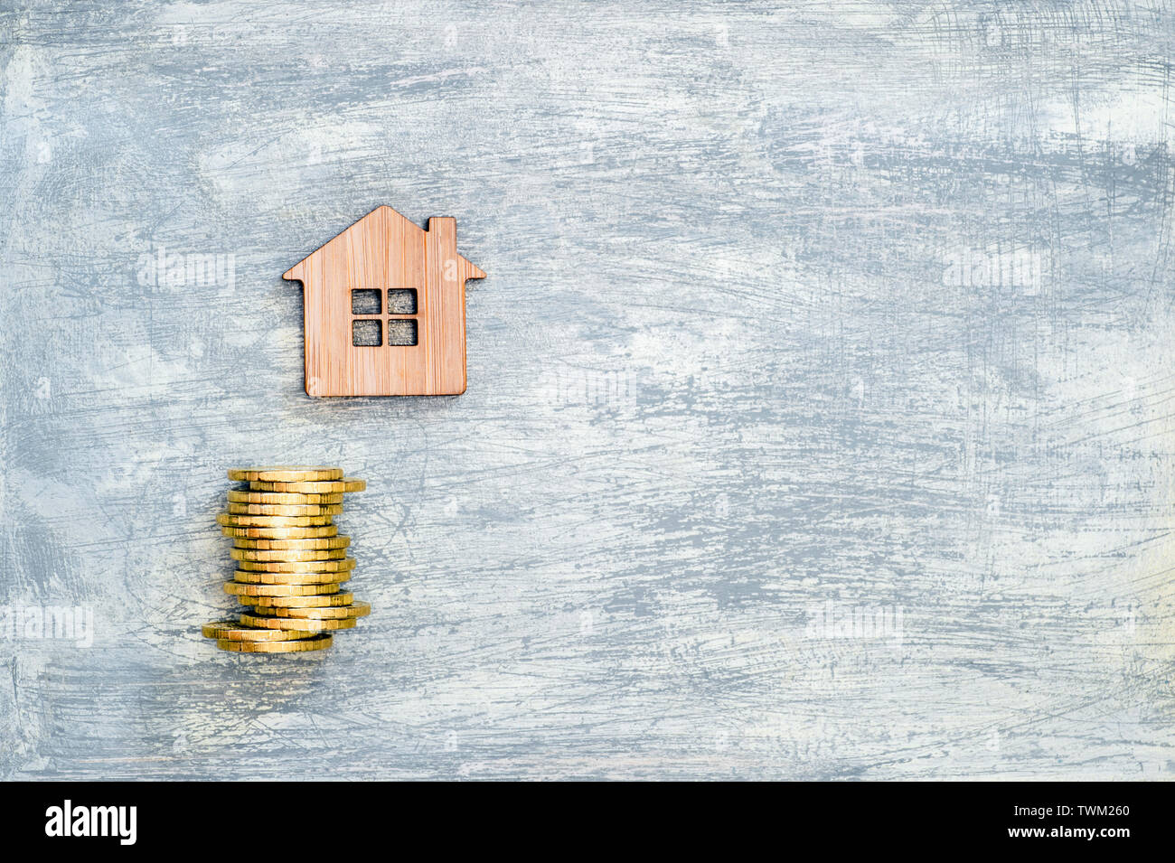 The house symbol is made of bamboo and yellow shiny coins on a scratched concrete gray background. The concept of the offer of purchase of real estate Stock Photo