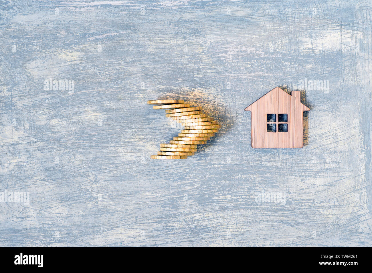 The house symbol is made of bamboo and yellow shiny coins on a scratched gray background with a blue tint. The concept of the offer of purchase of rea - Stock Image