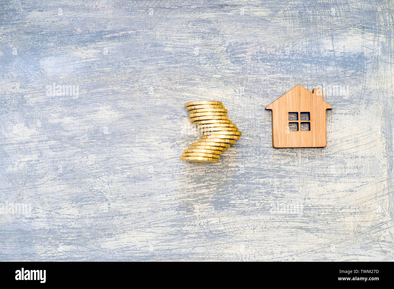 The house symbol is made of bamboo and yellow shiny coins on a scratched concrete gray background. The concept of the offer of purchase of real estate - Stock Image