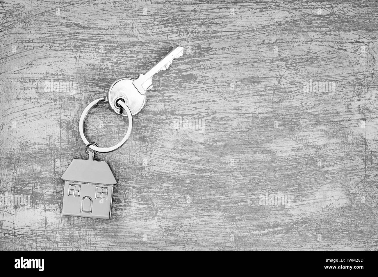 The symbol of a metal house with a key on a scratched concrete gray background. The concept of the offer of purchase of real estate and change of resi - Stock Image