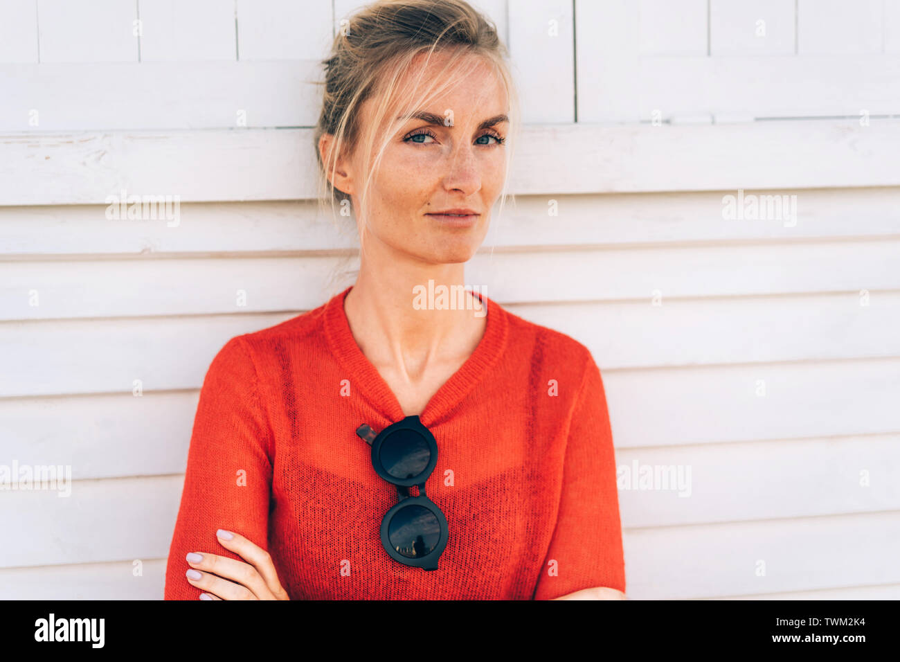 Natural beauty, authentic appearance, tanned blond woman with freckles on her face in a red sweater against the backdrop of a perfectly white planked - Stock Image