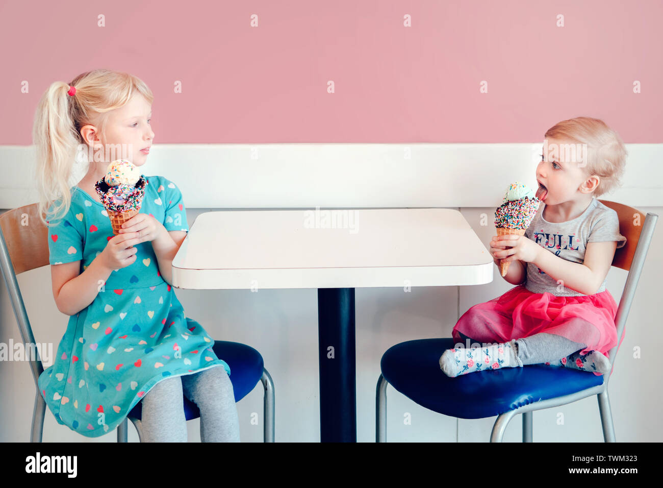 Lifestyle portrait of two happy Caucasian cute adorable funny children girls sitting together bragging boasting their ice-cream. Love envy jealous sis - Stock Image