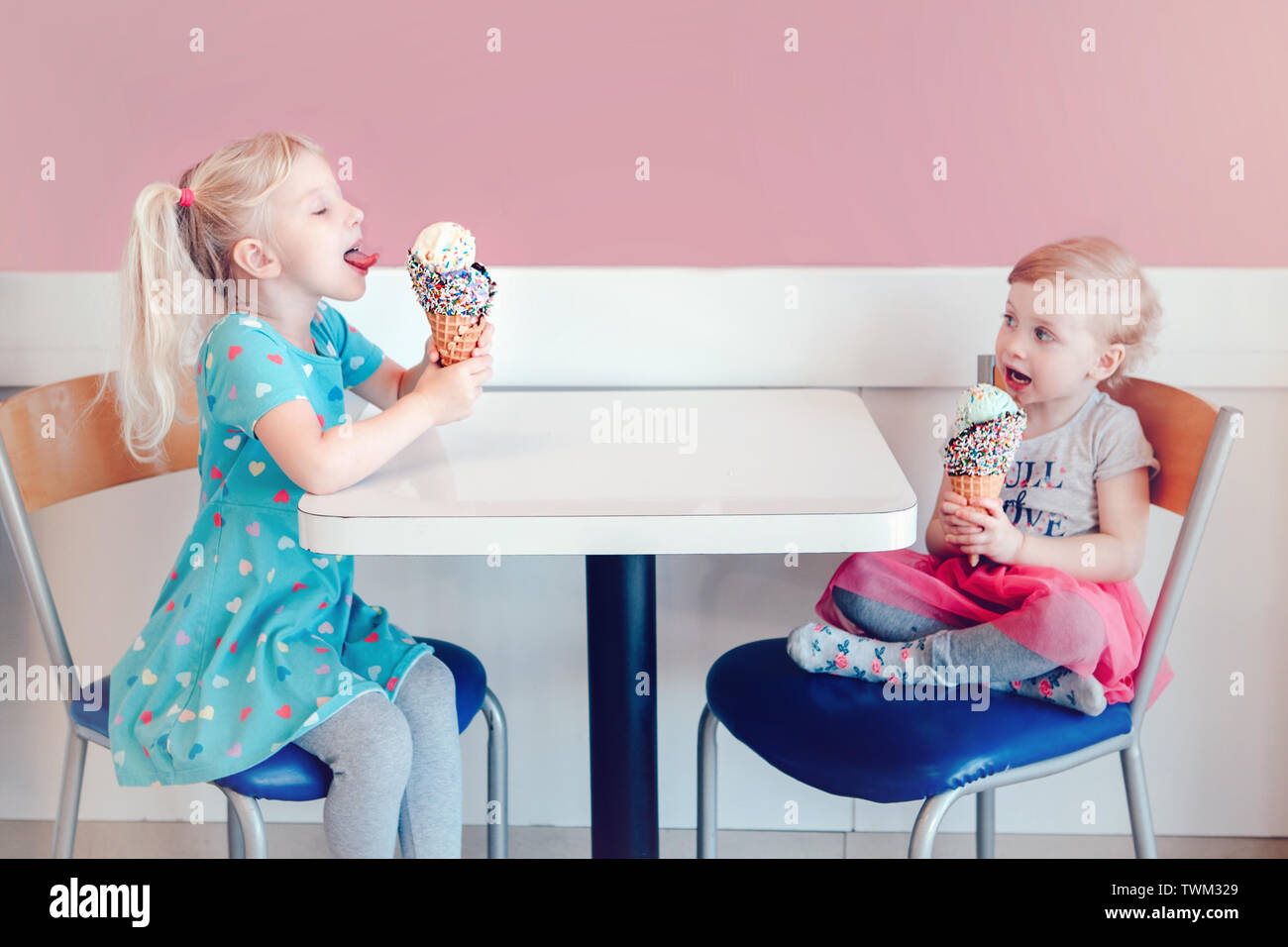 Lifestyle portrait of two happy Caucasian cute adorable funny children girls sitting together eating licking ice-cream with colorful sprinkles. Love e - Stock Image