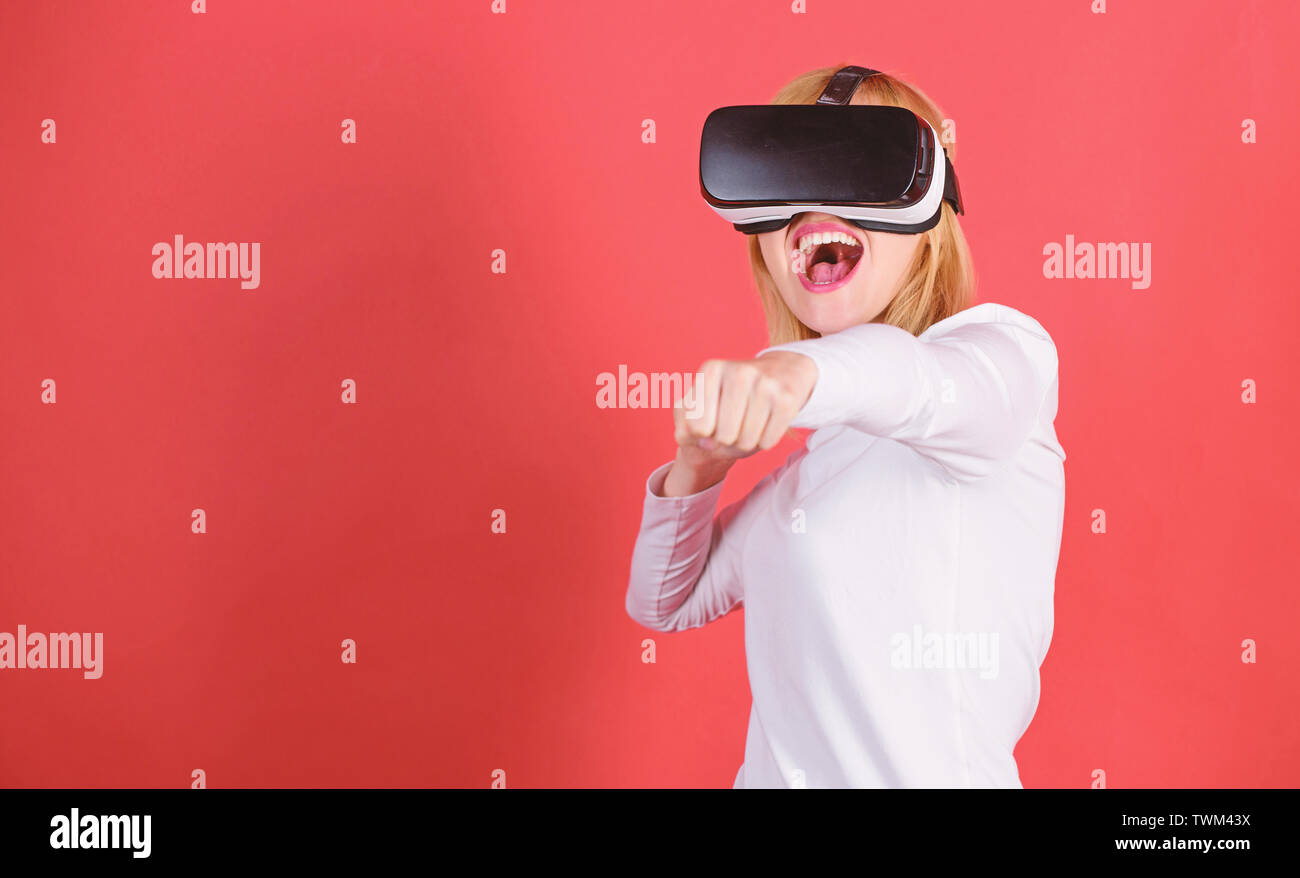Pretty woman playing game in virtual reality glasses. Portrait of an amazed girl using a virtual reality headset isolated on red background. Woman wit - Stock Image