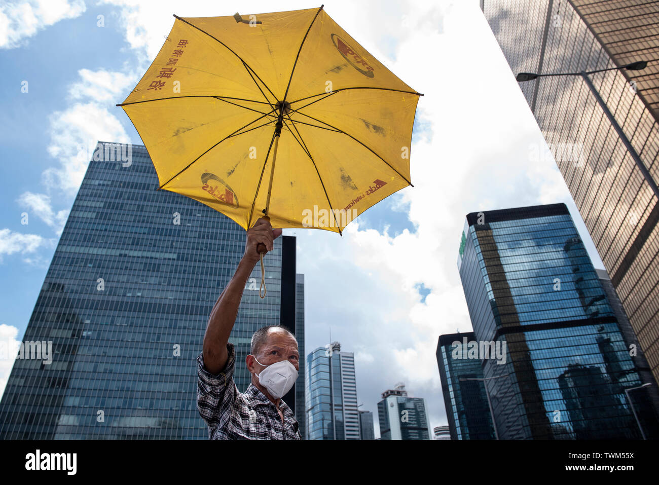 A protester holds a yellow umbrella, a symbol used during the Umbrella Movement, during the latest demonstration in Hong Kong. Despite the Chief Executive Carrie Lam's attempt to ease the heightened tension by agreeing to suspend the controversial extradition bill, student groups and union has continue the protest against Hong Kong government. The protesters called for the withdrawal of the controversial extradition bill, the release and non-prosecution of the people arrested due to the cause, investigation of whether excessive force had been used by the police on June 12, and the resignation - Stock Image