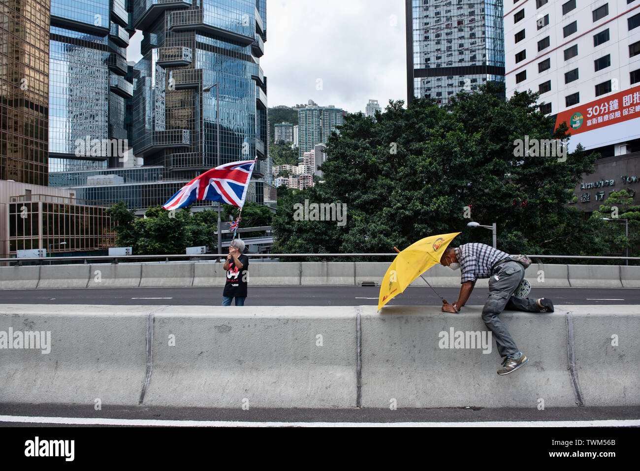 A protester waves the United Kingdom of Great Britain and Northern Ireland flag while another holds a yellow umbrella, symbol of the umbrella movement, while the roads have been blocked.  Despite the Chief Executive Carrie Lam's attempt to ease the heightened tension by agreeing to suspend the controversial extradition bill, student groups and union has continue the protest against Hong Kong government. The protesters called for the withdrawal of the controversial extradition bill, the release and non-prosecution of the people arrested due to the cause, investigation of whether excessive force - Stock Image