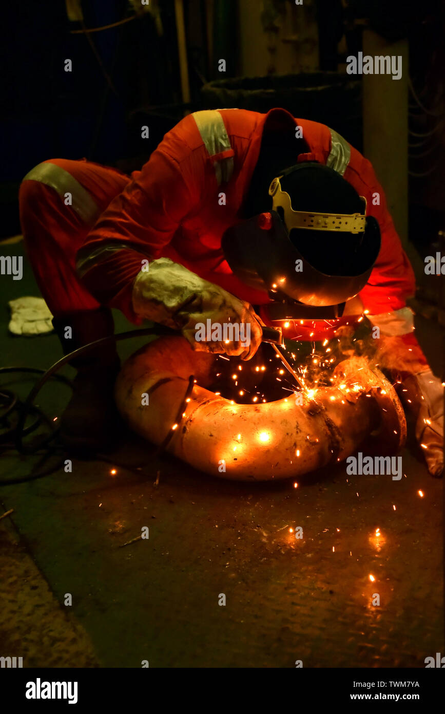 welder and his helper fabricate pipe in a workshop wearing with complete personal protective equipment - Stock Image