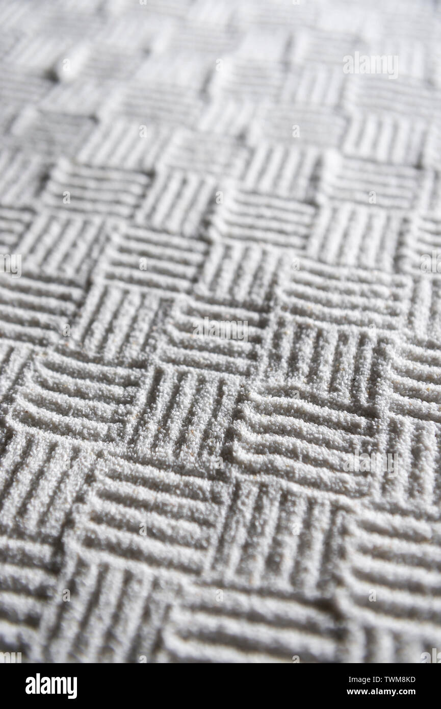 Woven cross-hatch pattern hand-raked into an abstract textured background in the monochrome white sand gravel of a Japanese Zen garden - Stock Image