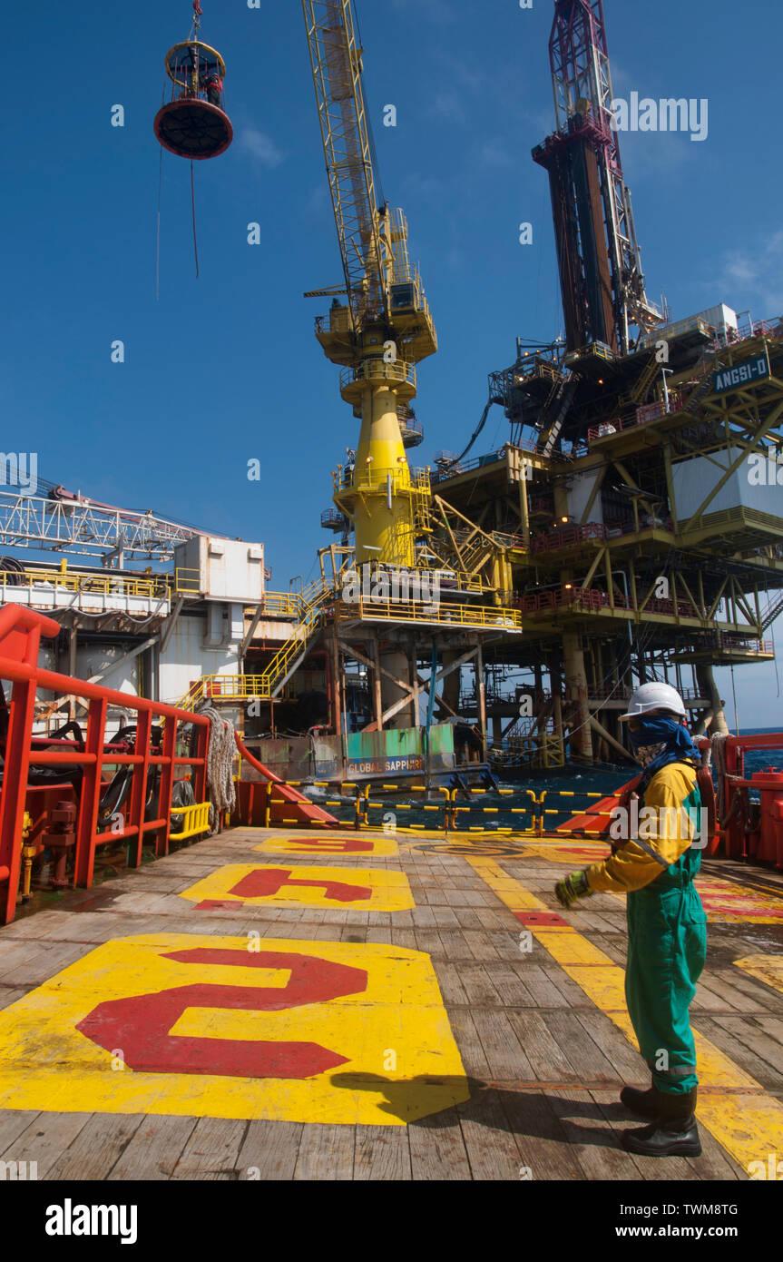 marine crew transferring oil platform personal from accommodation barge to vessel by crane - Stock Image