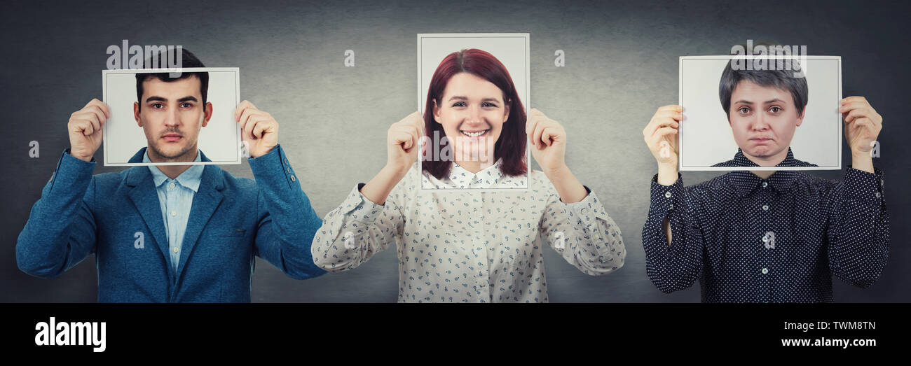 Tree people covering their faces using photo sheets with happy, sad and neutral emotions, like mask to hide real expression from society. Realist, opt - Stock Image