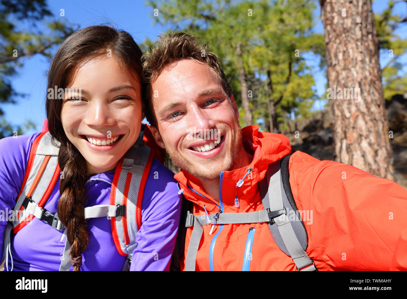 Selfie couple taking self-portrait hiking using smart phone camera in nature. Happy couple taking self-portrait photo picture looking at camera smilin - Stock Image