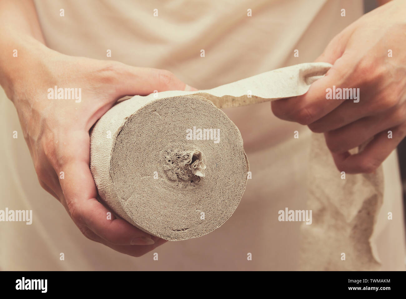 A woman holds a roll of toilet paper and is going to tear off part of it. - Stock Image