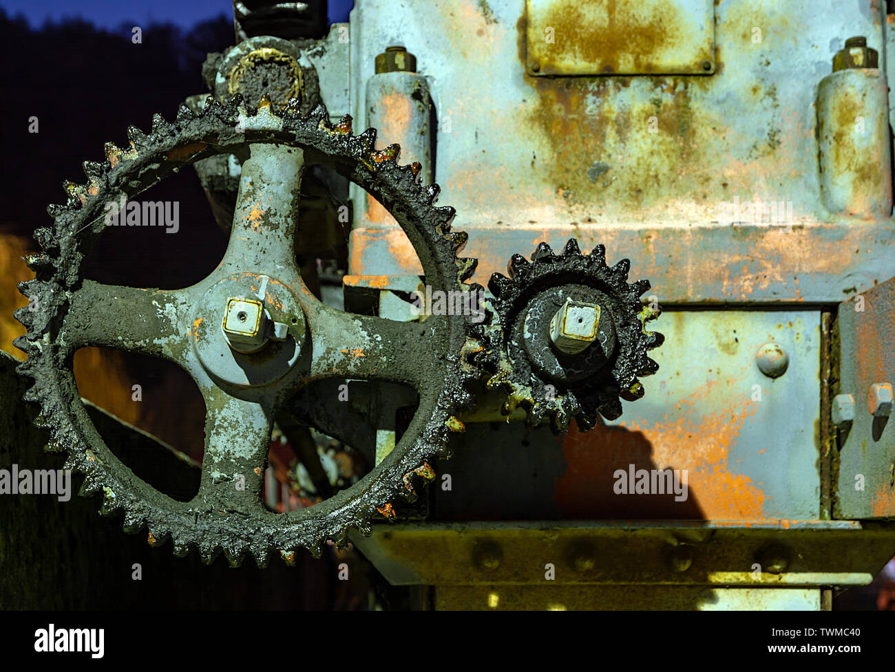 Vintage oily and rusty illuminated cogwheel at night - Stock Image