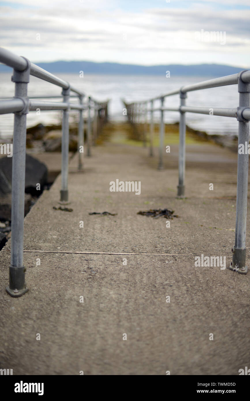 a pier with hand rails into a sea - Stock Image