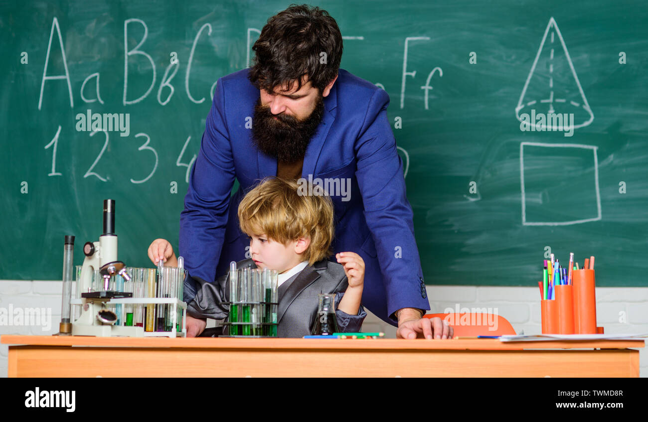 small boy with teacher man. Wisdom. Back to school. son and father at school. Pharmacy and chemistry theme. solution in research laboratory. Genetic research. Hand In Hand We Learn. - Stock Image