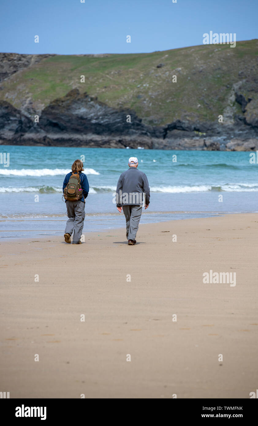 Elderly couple walking on the beach at Bedruthan Steps in Cornwall, England, UK Stock Photo