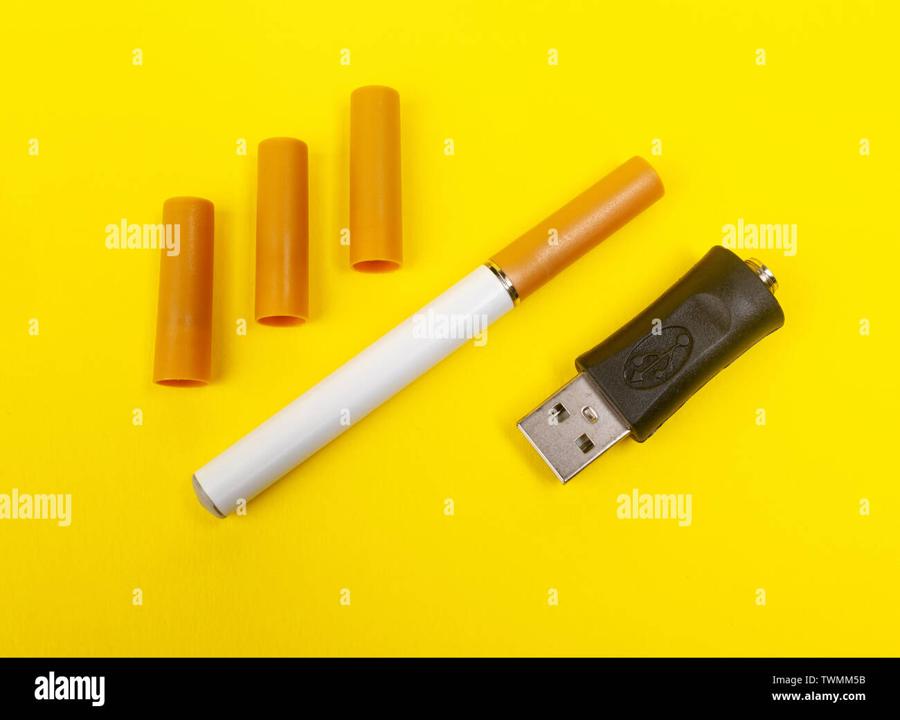 Closeup photo of an electronic cigarette on yellow background. - Stock Image