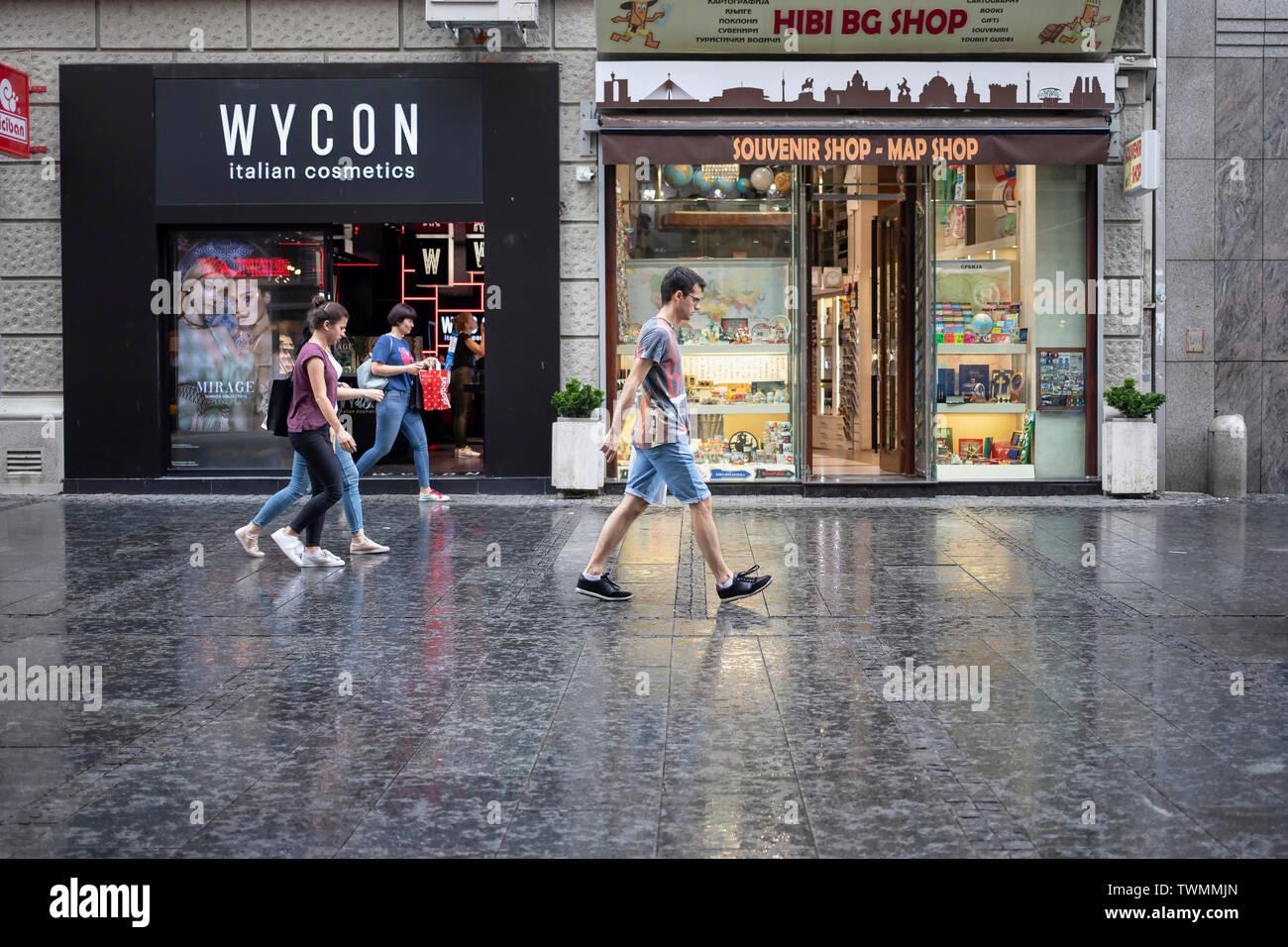 Belgrade, Serbia, June 18th 2019: Urban scene with people walking down the Knez Mihailova Street during the light rain - Stock Image