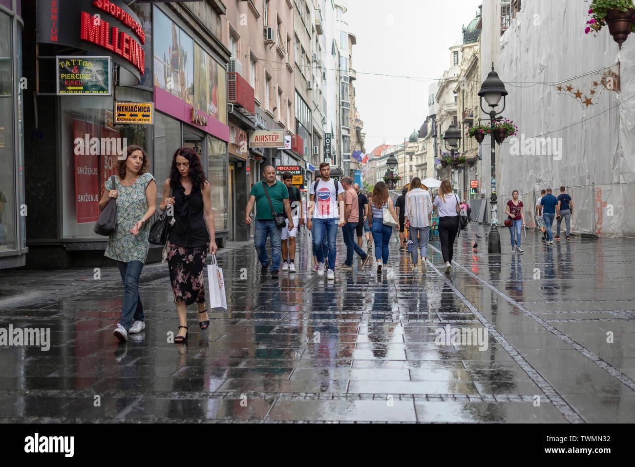 Belgrade, Serbia, June 18th 2019: Urban scene with people walking down the Knez Mihailova Street after spring rain - Stock Image