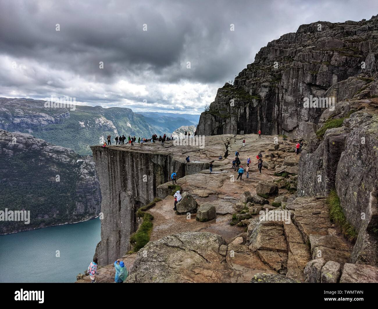 June 21, 2019 - Preikestolen, Norway - Hikers enjoy their time taking a break and making selfies on top of the fjord while at Pulpit Rock (Preikestolen) in Norway. (Credit Image: © Sachelle Babbar/ZUMA Wire) - Stock Image