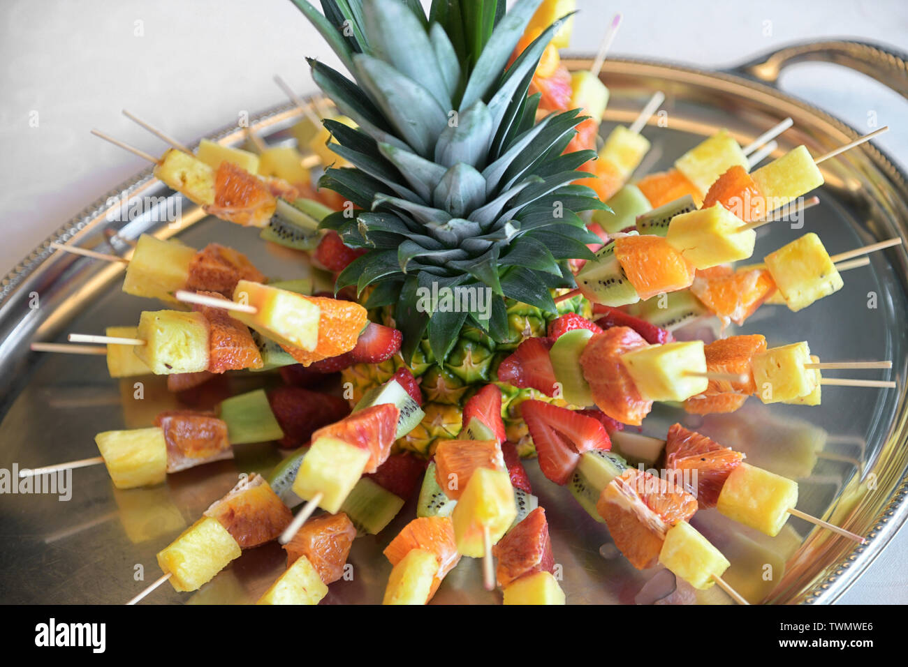 Fresh tropical fruit kebabs or skewers radiating from a pineapple with leaves threaded with diced pineapple, citrus, melon and strawberries in a close - Stock Image