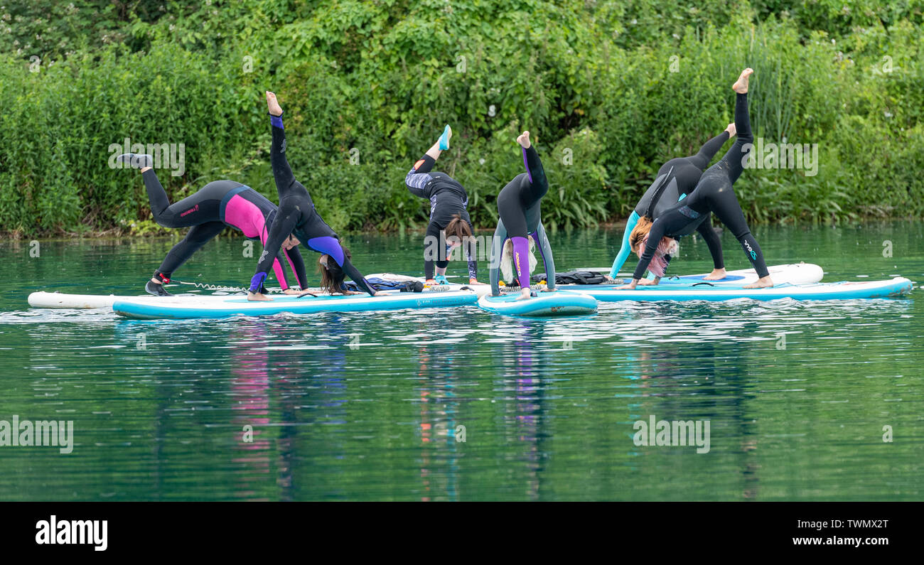 Upminster, Essex, UK. 21st June 2019. A new wellness initiative was launched today by Yogactive: Stand up Paddleboard Vinyasa yoga held at Stubbers Adventure Centre Upminster Essex Credit Ian Davidson/Alamy Live News - Stock Image
