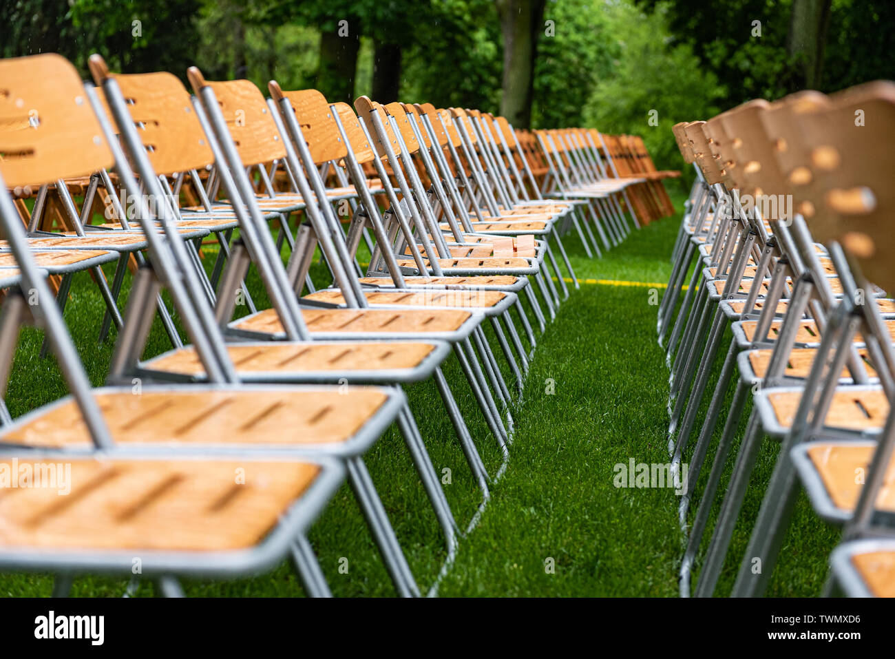Wooden chairs close-up stand outside in the park in the rain. Empty auditorium, green grass, trees and chairs with water drops. - Stock Image