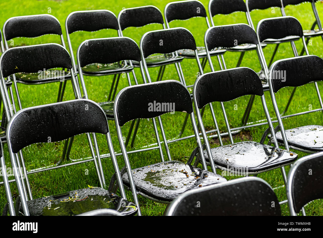 Black metal chairs stand outside in the park in the rain. Empty auditorium, green grass, trees and chairs with water drops. - Stock Image