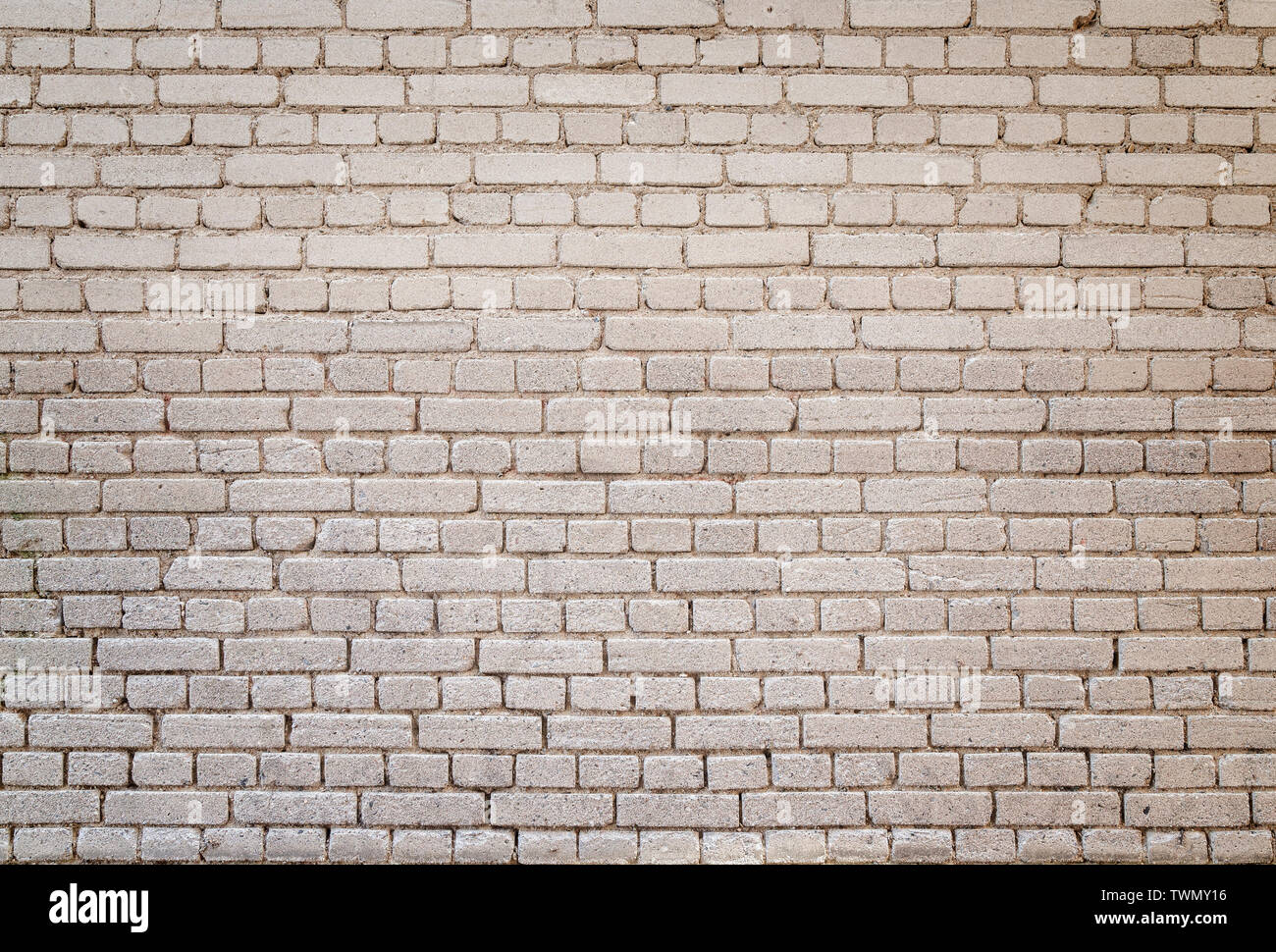 High resolution full frame background of detailed old pale brick wall with vignetting. Stock Photo
