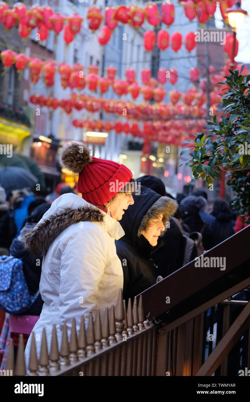 Diners peruse restaurant menu outside London's Chinatown with Chinese lanterns in the background - Stock Image