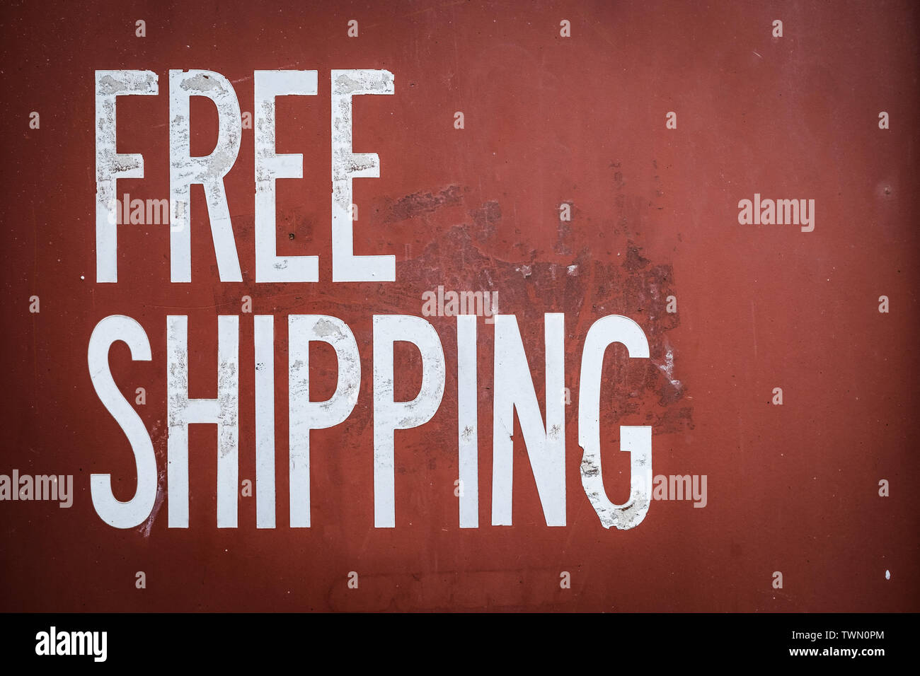 Grungy Free Shipping Sign On The Side Of A Red Metal Shipping Container Stock Photo