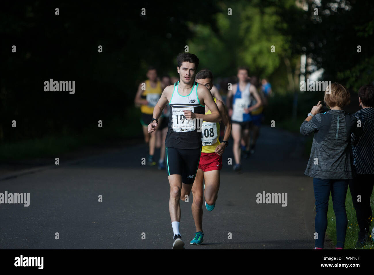 Glasgow, Scotland. 21st June, 2019. The Brian Goodwin Memorial 10km road race, hosted by Bellahouston Harriers running club, and held in Glasgow's scenic Pollok Country Park, was tonight won by Olympian Callum Hawkins in a time of 29minutes 06secs. (Hawkins wears Bib 199, Kilbarchan AAC); 2nd male was Jamie Crow (Bib 108, Central AC)) with a Personal Best time of 29min 43sec, and 3rd male was James Donald (30:11, Bib 130, Dundee Hawkhill Harriers).  Credit: jeremy sutton-hibbert/Alamy Live News - Stock Image