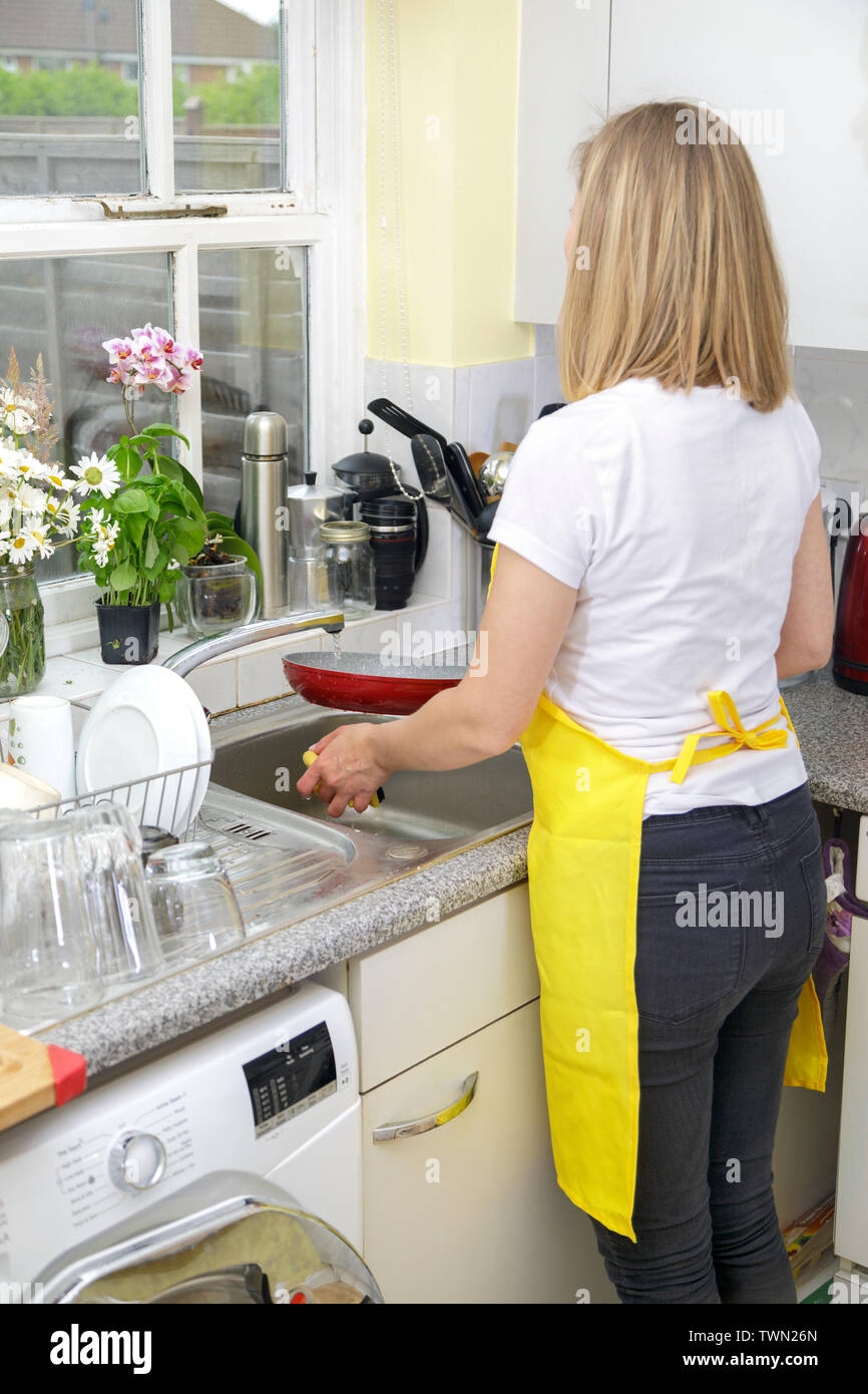 Young Woman in yellow apron washing dishes and cleaning kitchen. Housekeeper washes pate in sink. Domestic life Stock Photo