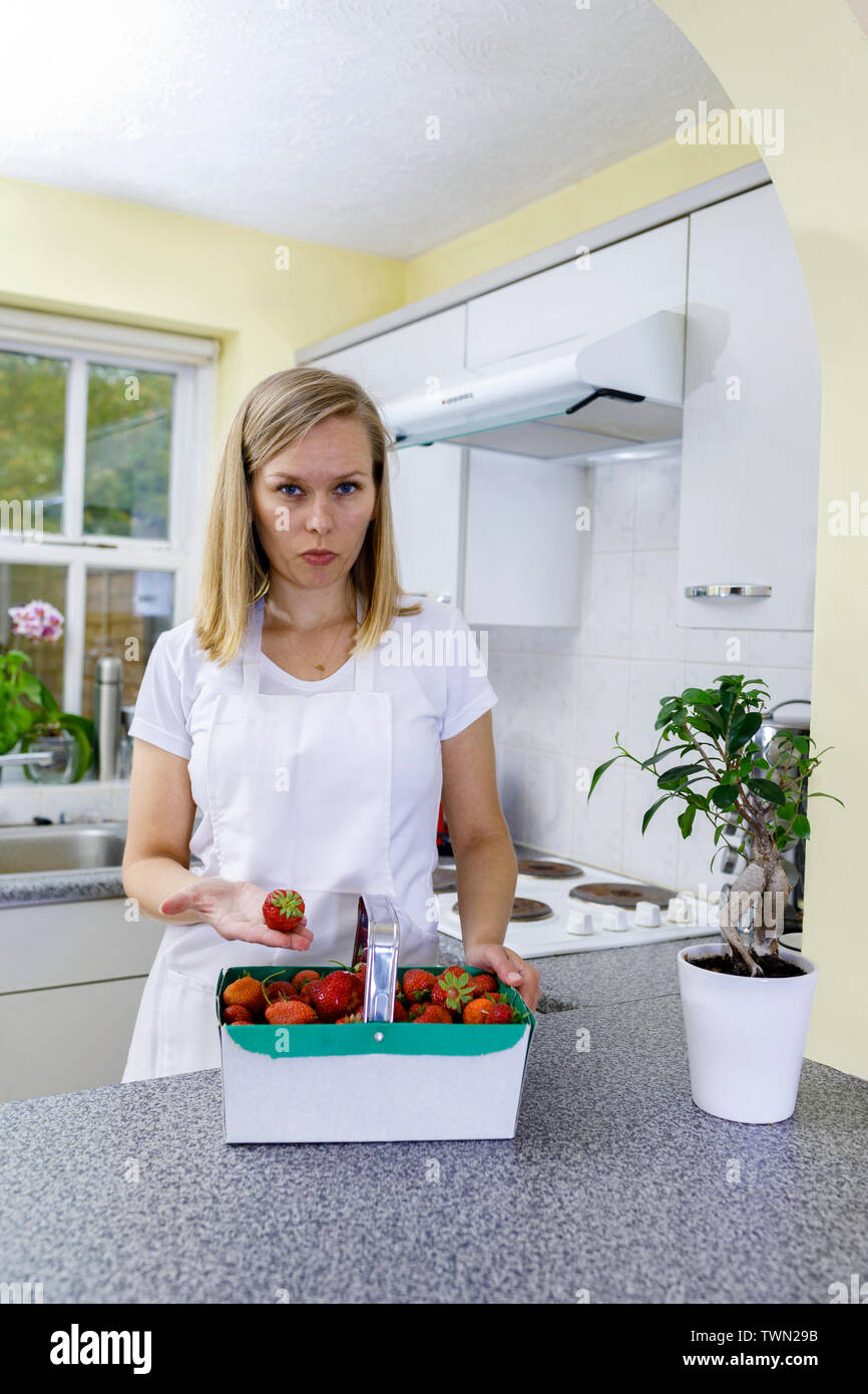 Young Woman cooking at home. Girl is holding basket of organic strawberries in kitchen. Fresh strawberries straight out of garden are being prepared b - Stock Image