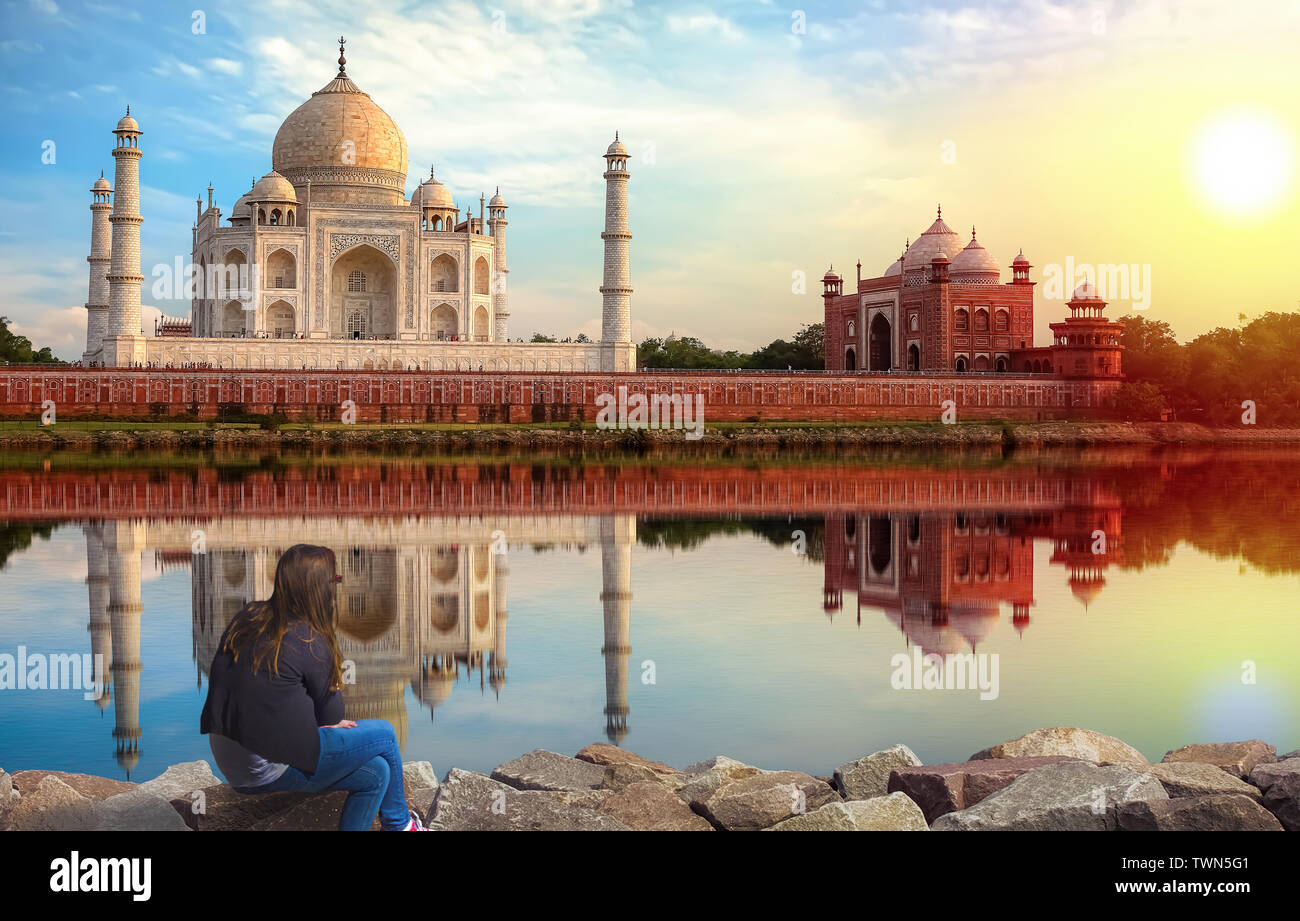 Taj Mahal Agra sunset view with young female tourist enjoying the view from Mehtab Bagh on the banks of river Yamuna Stock Photo