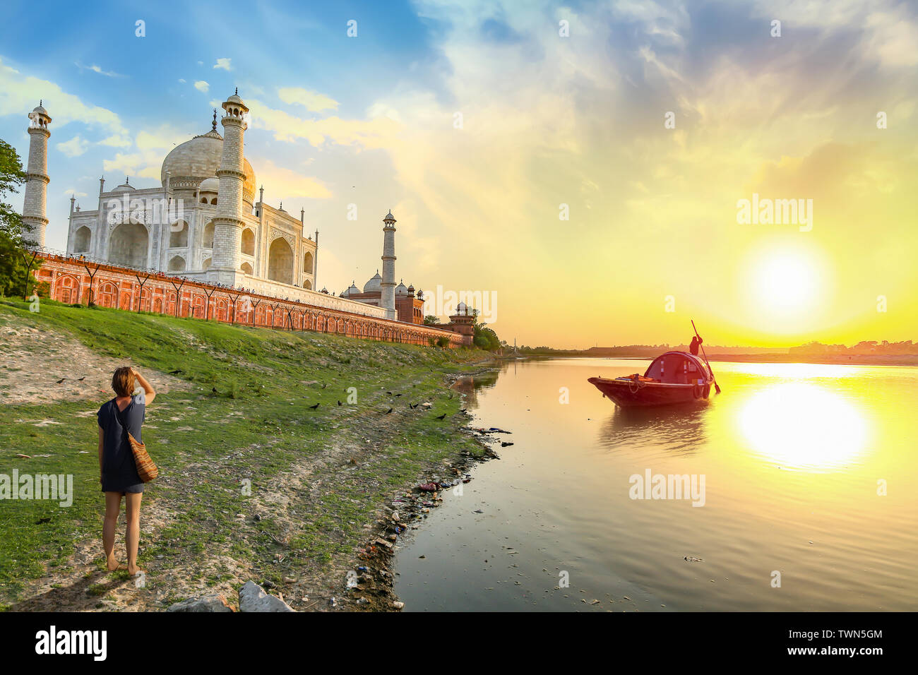 Taj Mahal at sunset with view of boat on river Yamuna at Agra India. Taj Mahal is a UNESCO World Heritage site and mughal architecture masterpiece Stock Photo
