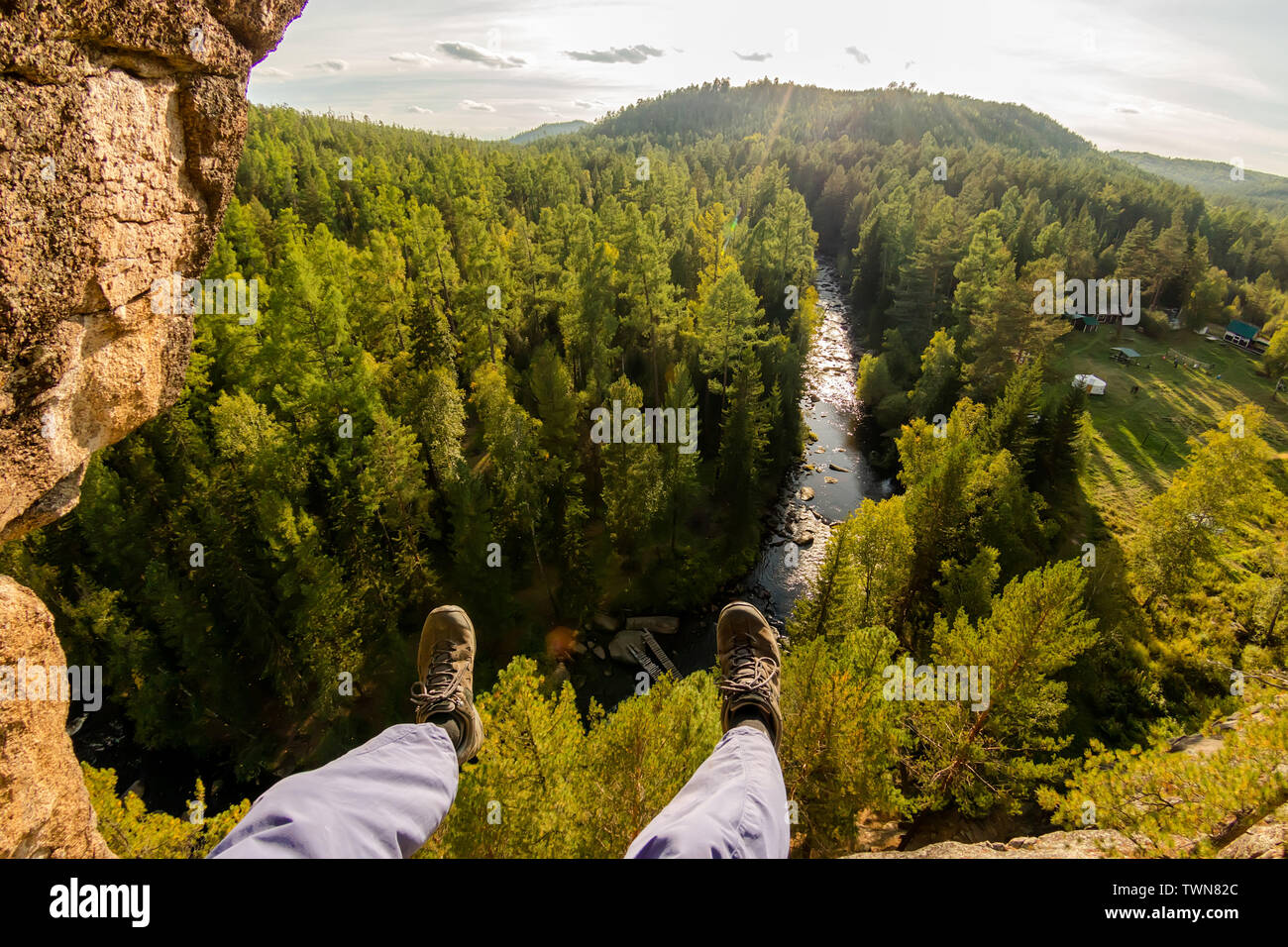 Climber's legs hanging on a rope in a harness, first person view to river in forest - Stock Image